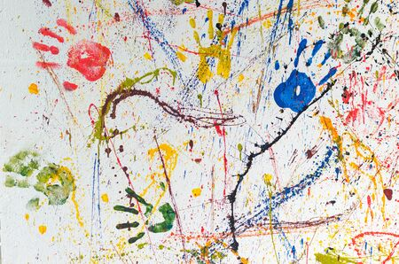 white wall: Multiple colorful children hand prints on white wall.