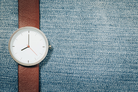 clock face: retro style,watch on blue jeans background Stock Photo