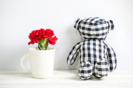 red  carnation: Teddy bear and red Carnation flower on wood table. Stock Photo