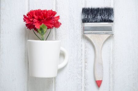 red  carnation: red Carnation flower in a cup and paint brush on white wooden  background