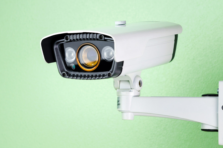 deterrent: white CCTV security camera on green wall.
