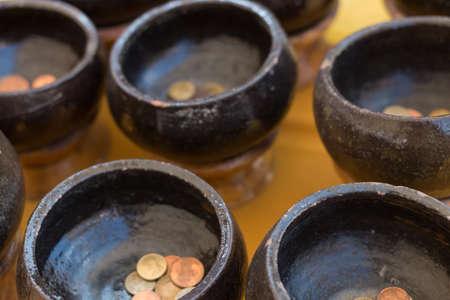 limosna: Taz�n monje negro con monedas limosnas Foto de archivo
