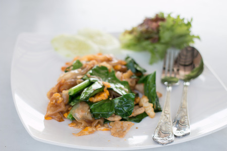 fried thin noodles with soy sauce in white dish photo