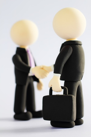 Two businessmen (doll) handshake (focus briefcase) photo