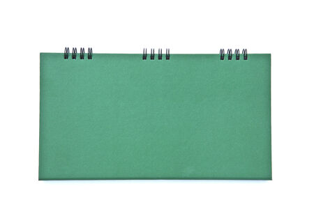 A green desk calendar background with the ring binder on top isolated on white background. The green paper is rough texture and tough. Stock Photo