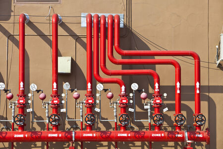 red water: splinker alarm system, red water pipe, brown wall, outdoor