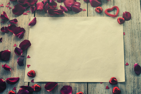 old paper and rose petals on wood background, vintage filtered photo 免版税图像 - 36571898