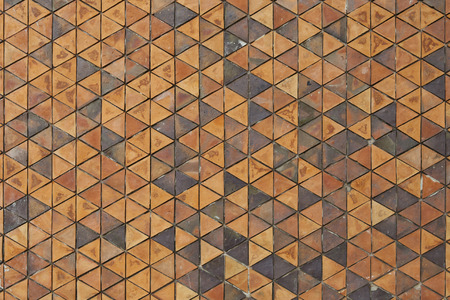 terra cotta: Pattern of triangular clay tiles, honeycomb tile pattern, yellow wall Stock Photo