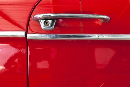 door handle of old bright red car surface texture background and copy space photo