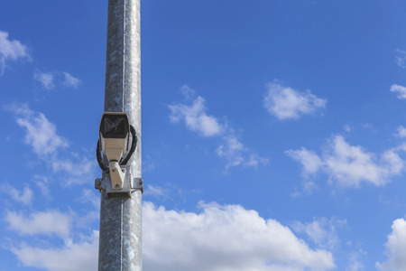 front view of single cctv on metal light pole, blue sky background photo