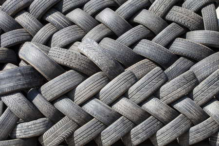 reusable: black rubber tires stacked zigzag, car wheel, garbage from vehicles, abstract art background, recycle object, reusable material Stock Photo