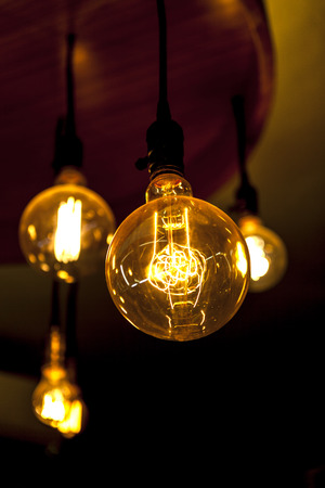 Four glowing tungsten lamps on dark background, vertical photo 免版税图像