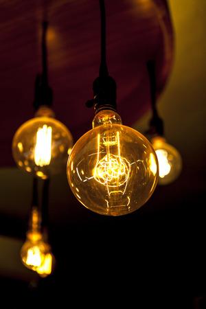 tungsten: Four glowing tungsten lamps on dark background, vertical photo Stock Photo