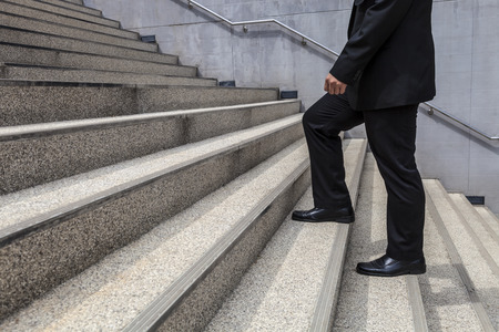 promoted: businessman is going up on large stair fight promoted Stock Photo