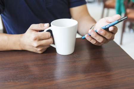 man's hands holding a cup of coffee and smartphone 免版税图像