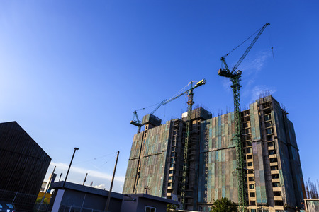 construction of high-rise buding by tower cranes and the canvas to protect the dust on blue sky background 免版税图像