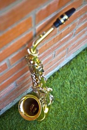 blass saxophone on grass lean against brick wall, top view, blow musical instrument 免版税图像