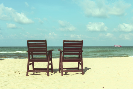 doublet: two chairs on the beach, vintage filter photo