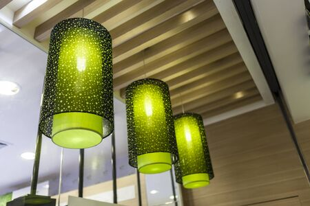 three green chandelier made by cloth hanging on decorative ceiling 免版税图像