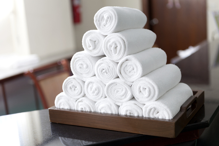 washup: rolled white body towels in wooden tray