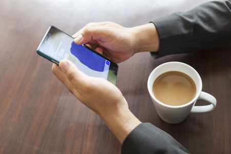 businessman playing smartphone during coffee brake