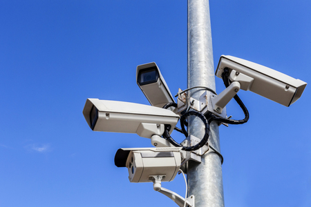 four cctv on metal light pole, blue sky background 免版税图像