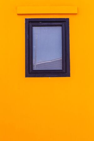 glass windows with black wood frame on bright yellow, colorful wallpaper