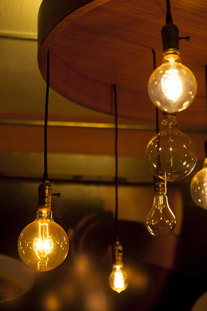 glowing and broken round bulb tungsten lamps on ancient chandelier, heated filament light, incandescent illumination on dark background
