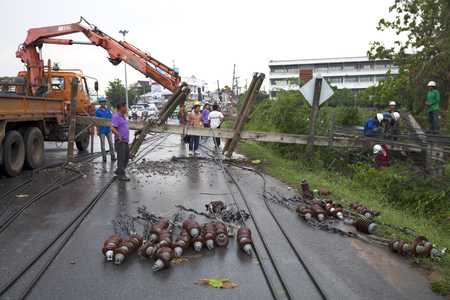 MUENG, MAHA SARAKHAMTHAILAND MAY 2015: Electrical insulators on road surface by engineer dismantling the wreckage of a high-voltage pylons due to heavy rain disaster on May 12, 2015 in Maha Sarakham. 新闻类图片
