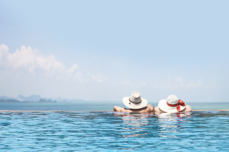 tourism: male and female models in the swimming pool wearing hats facing to the sea, beautiful summer vacation poster background, happy tour, enjoy travel, tourism, fun trip