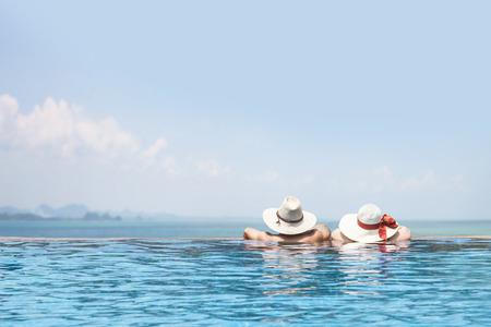 luna de miel: modelos masculinos y femeninos en la piscina con sombreros frente al mar, cartel hermoso fondo de vacaciones de verano, feliz viaje, disfrutar de los viajes, el turismo, viaje de diversión