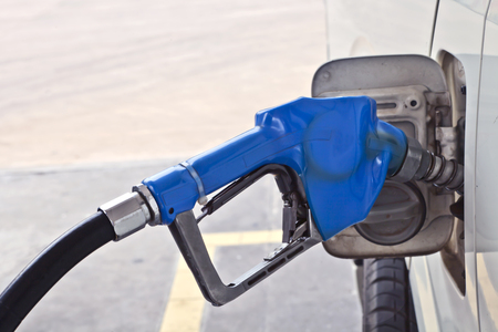 benzene: A blue fuel dispenser connecting to the car, add fuel, put in gasoline, benzene, diesel Stock Photo