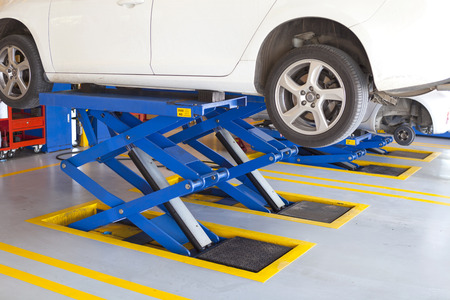choke: scissor cranes lift white car up for wheel tire replacement in garage