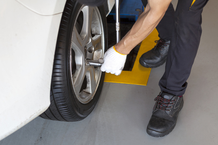 car wheel tire replacement on floor by mechanic in the garage