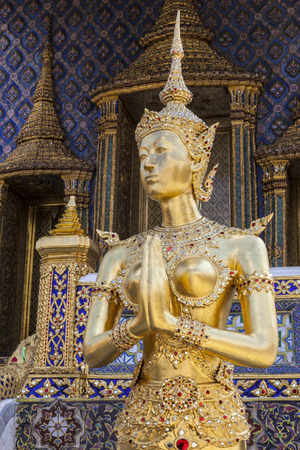 back view of a graceful golden kinaree image on blue sky background, Thai myth animal art at wat phra kaew, Bangkok, Thailand 免版税图像