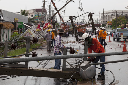 MUENG, MAHA SARAKHAMTHAILAND MAY 2015: Electrical engineers salvaging wreckage of lighting poles  pylons by heavy rain disaster in evening of May 12, 2015 in Maha Sarakham. Near Vocational college. 新闻类图片
