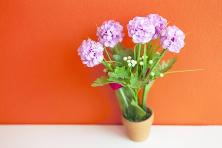 lovely pink artificial hydrangea flower made from cloth on bright orange wall, wallpaper background