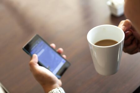 realtime: coffee cup and smartphone in a man hand Stock Photo