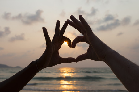 romantic man and woman hands making the heart shape on twilight sea and sky background
