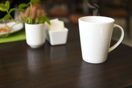 white coffee cup on wooden breakfast table