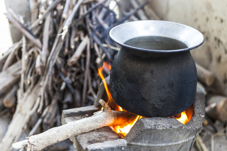 black pot boiling water for cooking on the fired stove next to firewood pile, Thailand Esan traditional culture ancient method