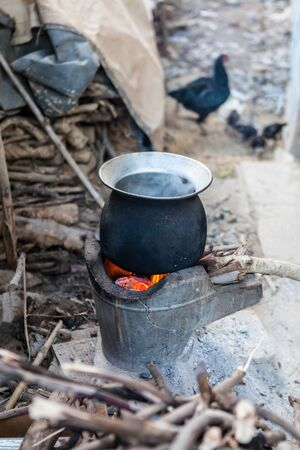 evaporating: black boiling pot for cooking on stove next to the plywood pile