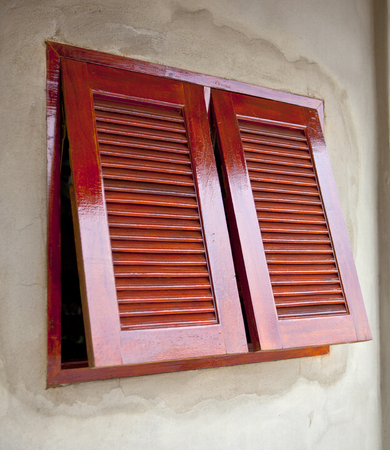 lacquer red wooden shuttered windows on cement wall