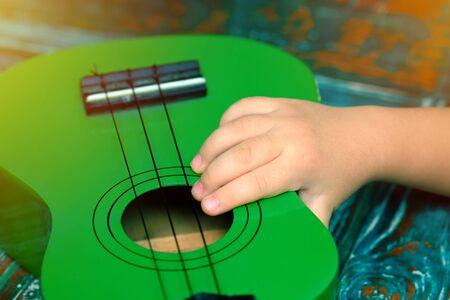 Kid hand holding a little ukulele Stok Fotoğraf