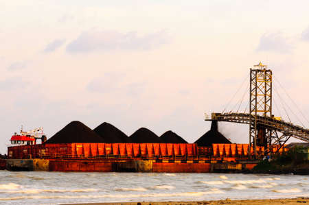 mining ships: coal flow from loading conveyor to barge in indonesia