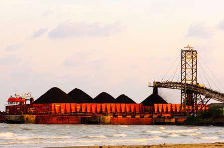 mijnbouw: steenkool stroom van geladen transportband naar binnenschip in Indonesië Stockfoto
