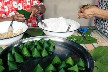 man and woman are confederate to Wrapped in local sweets with banana leaf   In occasion of Family Day and Songkran Festival of Thailand