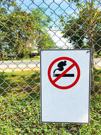 Non smoking sign hanging wire mesh fence in the garden