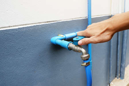 Use hand to twist the faucet to turn on the water at The back wall of the house