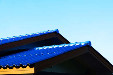 view of blue cement tile roof with sky in afternoon